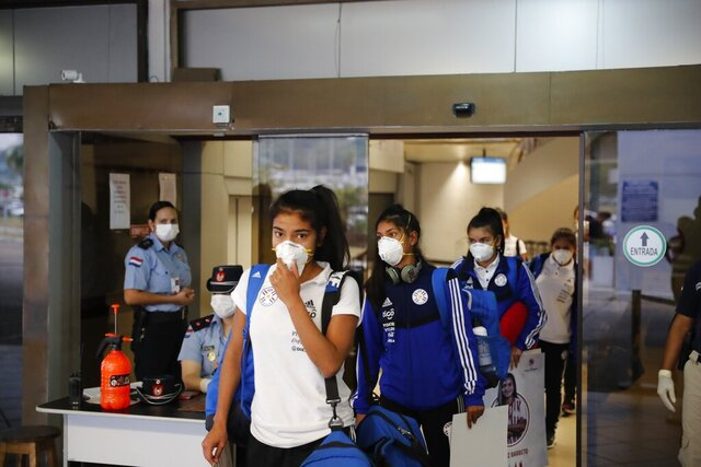 FILE - In this March 13, 2020, file photo, Paraguay's U20 women's soccer team members arrive at the airport in Luque, near Asuncion, Paraguay, after the tournament being played in San Luis, Argentina was suspended. The  global players' association released its report on the state of  women's soccer, after warning that the coronavirus  outbreak could have a disastrous impact following the gains of last summer's Women's World Cup.  (AP Photo/Jorge Saenz, File)
