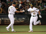 Oakland Athletics' Marcus Semien, right, celebrates with third base coach Matt Williams after hitting a two-run home run off New York Yankees' J.A. Happ during the third inning of a baseball game Wednesday, Aug. 21, 2019, in Oakland, Calif. (AP Photo/Ben Margot)