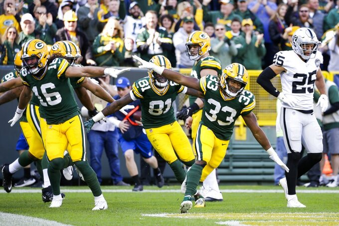 Green Bay Packers' Aaron Jones celebrates his touchdown catch during the first half of an NFL football game against the Oakland Raiders Sunday, Oct. 20, 2019, in Green Bay, Wis. (AP Photo/Jeffrey Phelps)