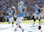 North Carolina's Beau Corrales (15) celebrates as he runs for a touchdown while teammates Carl Tucker (86) and Ed Montilus (63) look on during the second quarter of an NCAA college football game against Clemson in Chapel Hill, N.C., Saturday, Sept. 28, 2019. (AP Photo/Chris Seward)