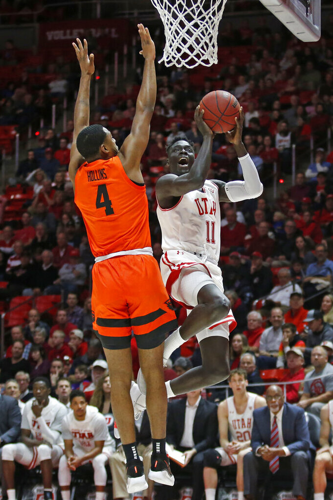 Utah guard Both Gach (11) goes to the basket as Oregon State forward Alfred Hollins (4) defends in the second half during an NCAA college basketball game Thursday, Jan. 2, 2020, in Salt Lake City. (AP Photo/Rick Bowmer)