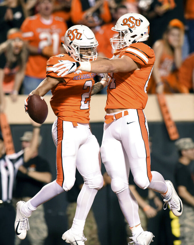 Oklahoma State wide receiver Tylan Wallace, left, celebrates with Logan Carter after scoring in the first half of an NCAA college football game in Stillwater, Okla., Saturday, Oct. 27, 2018. (AP Photo/Brody Schmidt)