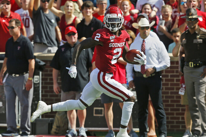 Oklahoma wide receiver CeeDee Lamb (2) looks over his shoulder as he carries the ball in for a touchdown in the second quarter of an NCAA college football game against Texas Tech in Norman, Okla., Saturday, Sept. 28, 2019. (AP Photo/Sue Ogrocki)