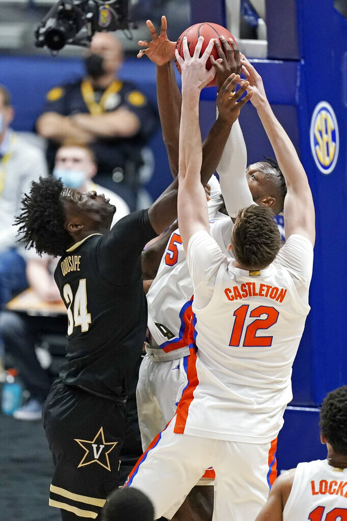 Vanderbilt's Akeem Odusipe (34) reaches for a rebound with Florida's Colin Castleton (12) in the first half of an NCAA college basketball game in the Southeastern Conference Tournament Thursday, March 11, 2021, in Nashville, Tenn. (AP Photo/Mark Humphrey)