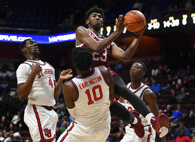 Massachusetts' T.J. Weeks, center top, is fouled by St. John's Marcellus Earlington (10) as St. John's Greg Williams Jr., left, and Rasheem Dunn, right, defend during the first half of an NCAA college basketball game, Sunday, Nov. 24, 2019, in Uncasville, Conn. (AP Photo/Jessica Hill)
