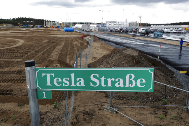 FILE - In this Wednesday, Sept. 2, 2020 file photo, a street sign reading 'Tesla Street 1' stand in front of the construction site of the electric car Tesla Gigafactory in Gruenheide near in Berlin, Germany. A German utility company says it has shut down the pipes supplying Tesla with water for the construction of a factory near Berlin because the automaker hasn't paid its bills. A spokeswoman for the company WSE said Thursday, Oct. 15 that Tesla was given repeated warnings its water supply would be turned off.  (AP Photo/Michael Sohn, file)