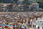People sunbathe in Saint Jean de Luz' beach, southwestern France, Saturday, July 18, 2020. New French Prime Minister Jean Castex has announced that respiratory masks will be mandatory in France in closed public places as of