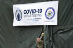 A member of the National Guard assisting at a COVID-19 mobile testing location looks out of a tent used for drive-thru tests, Tuesday, Dec. 1, 2020, in Auburn, Maine. Amid the coronavirus resurgence, states have begun reopening field hospitals to handle an influx of sick patients that is pushing health care systems — and their workers — to the breaking point. Hospitals are bringing in mobile morgues. And funerals are once again being livestreamed or performed as drive-by affairs. (AP Photo/Robert F. Bukaty)