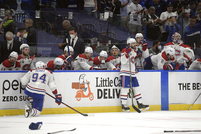 The Montreal Canadiens watch as the Tampa Bay Lightning celebrate the series win in Game 5 of the NHL hockey Stanley Cup finals, Wednesday, July 7, 2021, in Tampa, Fla. (AP Photo/Phelan Ebenhack)