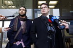 Former Guantanamo Bay prisoner Omar Khadr, left, and his lawyer Nathan Whitling speak after court in Edmonton on Monday March 25, 2019. A judge ruled Monday that Omar Khadr has completed his sentence. Monday's ruling means he no longer faces the threat of returning to prison.   (Jason Franson/The Canadian Press via AP)