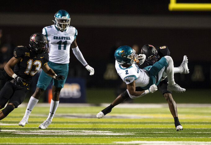Appalachian State defensive back Steven Jones Jr. (6) tackles Coastal Carolina running back Reese White (2) during the second half of an NCAA college football game Wednesday, Oct. 20, 2021, in Boone, N.C. (AP Photo/Matt Kelley)
