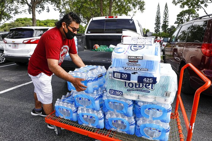 Lake Worth, Fla., resident Juan Avila stocks up on water and paper towels at the Lantana, Fla Costco as Hurricane Isaias approaches the Florida coast Saturday, Aug. 1, 2020.   Isaias snapped trees and knocked out power as it blew through the Bahamas on Saturday and churned toward the Florida coast, where it is threatening to complicate efforts to contain the coronavirus in a hot spot.  (Damon Higgins/The Palm Beach Post via AP)