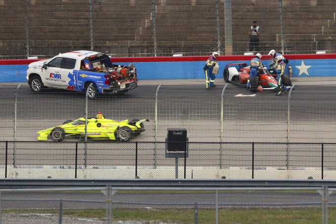 The IndyCar safety team assists James Hinchcliffe after his crash during the IndyCar Series auto race at Texas Motor Speedway on Saturday, May 1, 2021, in Fort Worth, Texas. (AP Photo/Richard W. Rodriguez)