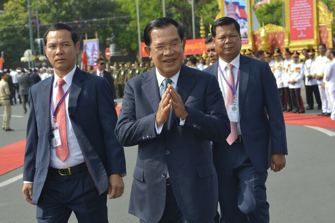 Cambodian Prime Minister Hun Sen, center, greets his government officers during the country's 66th Independence Day from France, at the Independence Monument in Phnom Penh, Cambodia, Saturday, Nov. 9, 2019. The leader of the banned Cambodia National Rescue Party, Sam Rainsy was boarding a fly in Paris for his attempt to return home to challenge his country's longtime autocratic leader as the security inside the country was on high alert and beefed up. (AP Photo/Vithy Soth)