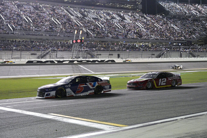 Kyle Larson (5) and Ryan Blaney (12) make their way down pit road during a NASCAR Cup Series auto race at Daytona International Speedway, Saturday, Aug. 28, 2021, in Daytona Beach, Fla. (AP Photo/Phelan M. Ebenhack)