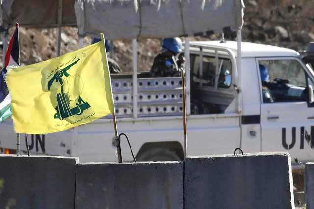 A UN patrol drives past a Hezbollah flag and a concrete barrier in southern Lebanon on the border with Israel, Wednesday, Aug. 26, 2020. Israeli attack helicopters struck observation posts of the militant Hezbollah group along the Lebanon border overnight after shots were fired at Israeli troops operating in the area, the military said Wednesday. (AP Photo/Ariel Schalit)