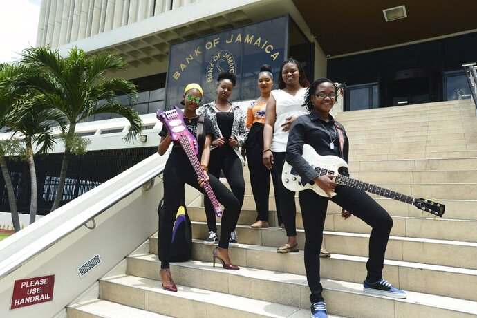 In this June 13, 2019 photo, members of the all-femalebandADAHEZ, Chevanese Palmer, from left, Karissa Palmer, Gabeana Campbell, Tashana Barnett and Shadeeka Daughma, pose for a photo on the steps of the Bank of Jamaica, in Kingston. Jamaica's central bank thinks the country's economy is doing very well and it is using an instantly recognizable symbol of the island to get this message to the people: reggae music. (AP Photo/Collin Reid)