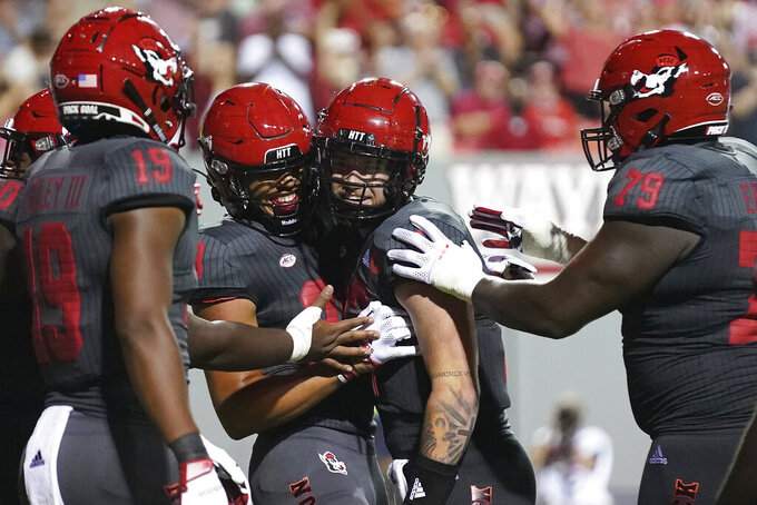 North Carolina State wide receiver C.J. Riley (19), wide receiver Christopher Toudle, second from left, quarterback Devin Leary and offensive tackle Ikem Ekwonu (79) celebrate Toudle's touchdown against South Florida during the second half of an NCAA college football game in Raleigh, N.C., Thursday, Sept. 2, 2021. (AP Photo/Gerry Broome)