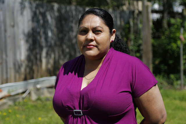 In a photo taken Thursday, May 7, 2020, Erika Romero poses for The Associated Press in her home in Hyattsville, Md. Romero joined millions of Americans out of work after she was recently laid off from her job as an office janitor. (AP Photo/Julio Cortez)