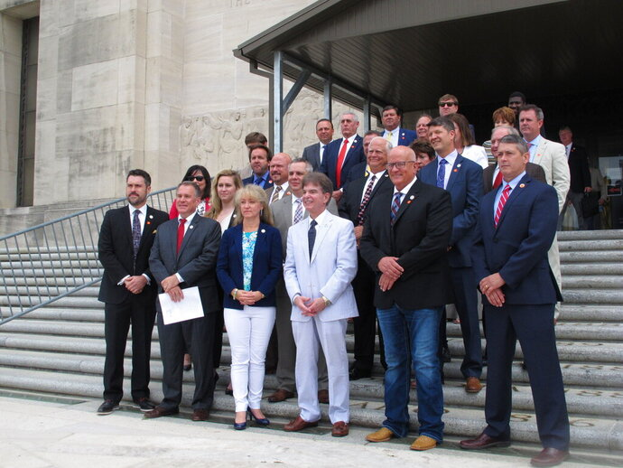 About two dozen House Republican lawmakers stand on the Louisiana Capitol steps in support of a petition that would end the state of emergency over COVID-19, on Wednesday, June 25, 2020, in Baton Rouge, La. The lawmakers have restarted a petition effort that failed to gain enough signatures earlier in the year, hoping to end the state of emergency declared by Democratic Gov. John Bel Edwards. (AP Photo/Melinda Deslatte)