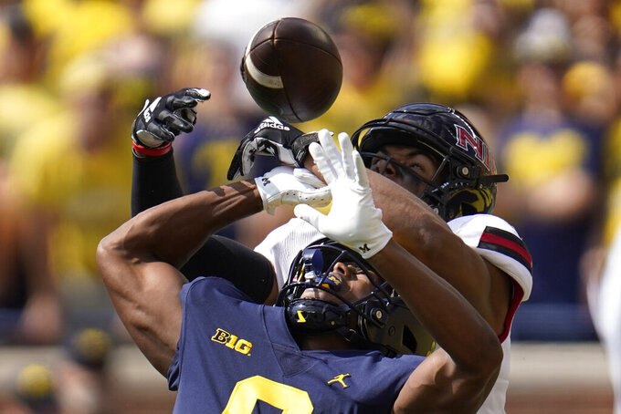 Northern Illinois cornerback Jordan Gandy (14) breaks up a pass intended for Michigan wide receiver Cornelius Johnson (6) in the first half of a NCAA college football game in Ann Arbor, Mich., Saturday, Sept. 18, 2021. (AP Photo/Paul Sancya)