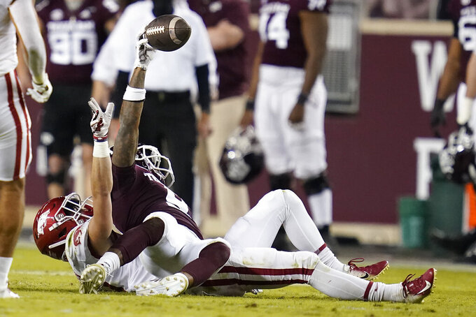 Texas A&M wide receiver Hezekiah Jones (9) reacts after a catch, and being tackled by Arkansas defensive back Hudson Clark (17) during the second quarter of an NCAA college football game Saturday, Oct. 31, 2020, in College Station, Texas. (AP Photo/Sam Craft)