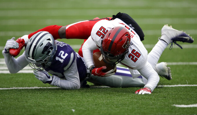 Kansas State defensive back AJ Parker (12) tackles Texas Tech running back Ta'Zhawn Henry (26) during the first half of an NCAA college football game in Manhattan, Kan., Saturday, Nov. 17, 2018. (AP Photo/Orlin Wagner)