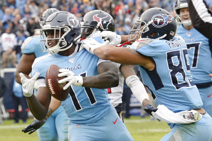 Tennessee Titans wide receiver A.J. Brown (11) celebrates with MyCole Pruitt (85) after Brown scored a touchdown against the Houston Texans in the second half of an NFL football game Sunday, Dec. 15, 2019, in Nashville, Tenn. (AP Photo/Mark Zaleski)