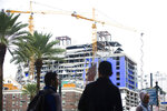 Pedestrians walk on Canal street near the Hard Rock Hotel construction site in New Orleans, Friday, Oct. 18, 2019. The Hard Rock Hotel partially collapsed last week leaving many workers injured, 3 confirmed dead. (Sophia Germer/The Advocate via AP)/