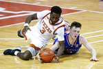 Texas guard Courtney Ramey (3) fights for a loose ball with Kansas guard Christian Braun during overtime in an NCAA college basketball game, Tuesday, Feb. 23, 2021, in Austin, Texas. (AP Photo/Eric Gay)