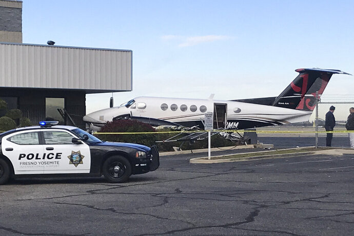 A small plane sits parked after it was crashed into a fence by a 17-year-old girl Wednesday, Dec. 18, 2019, at the Fresno Yosemite International Airport in Fresno, Calif. A spokeswoman for the airport told The Fresno Bee that the teenager breached the fence, started up the plane and crashed it into a fence Wednesday. Airport officials say officers found the teen in the pilot's seat, wearing the headset. No one was injured. The teen was arrested on suspicion of theft of an aircraft. (Jim Guy/The Fresno Bee via AP)
