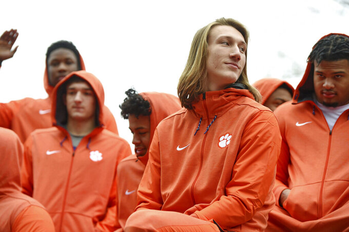 "FILE - In this Saturday, Jan. 12, 2019, file photo, Clemson quarterback Trevor Lawrence, foreground, and fellow freshmen ride in the parade honoring the football team, in Clemson, S.C., after the Tigers defeated Alabama 44-16 in the NCAA College Football Playoff championship game several days earlier. Lawrence was falsely quoted criticizing ""coastal elite media"" after the Clemson football team's White House visit on Monday, Jan. 14. (AP Photo/Richard Shiro, File)"