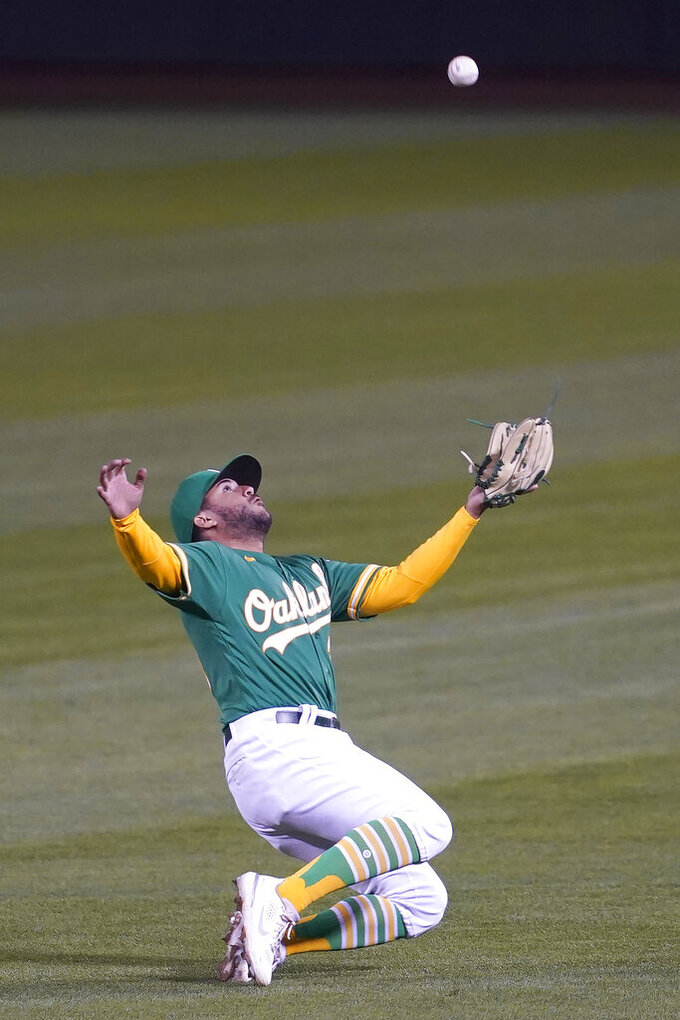 Oakland Athletics second baseman Vimael Machin catches a fly out hit by Minnesota Twins' Willians Astudillo during the fifth inning of the second baseball game of a doubleheader in Oakland, Calif., Tuesday, April 20, 2021. (AP Photo/Jeff Chiu)