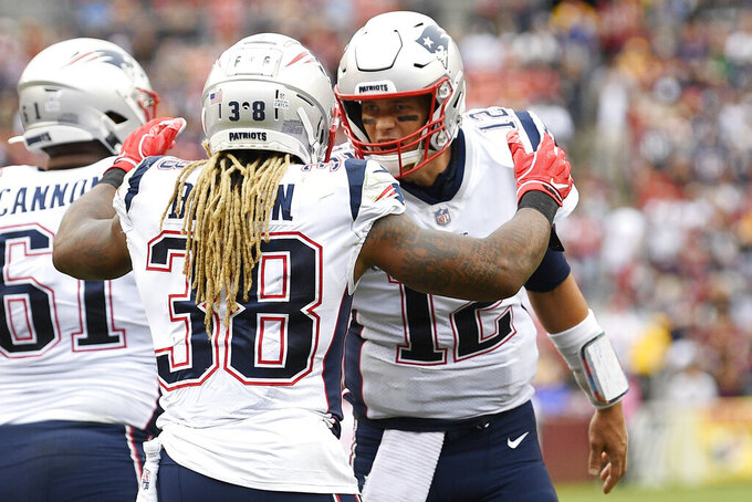 New England Patriots running back Brandon Bolden (38) celebrates his touchdpown with New England Patriots quarterback Tom Brady (12) against the Washington Redskins during the second half of an NFL football game, Sunday, Oct. 6, 2019, in Washington. (AP Photo/Nick Wass)