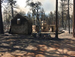 This photo provided by Rusty Bowers shows the remains of Arizona House Speaker Rusty Bowers family weekend home near several miles southeast of Miami, Ariz., Tuesday, June 8, 2021, that was destroyed by a wildfire the day before. Bowers used the home in the remote mountains as a family retreat and often did his artwork there. (Elijah Cardon/Rusty Bowers via AP)