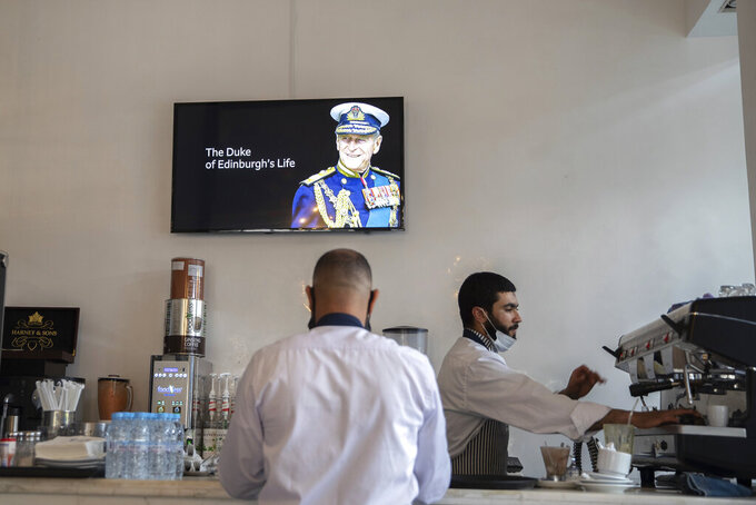 Waiters work at a coffeeshop while a TV shows the news of Prince Philip's death, in Rabat, Morocco, Friday, April 9, 2021. Prince Philip, the irascible and tough-minded husband of Queen Elizabeth II who spent more than seven decades supporting his wife in a role that both defined and constricted his life, has died, Buckingham Palace said Friday. He was 99. (AP Photo/Mosa'ab Elshamy)