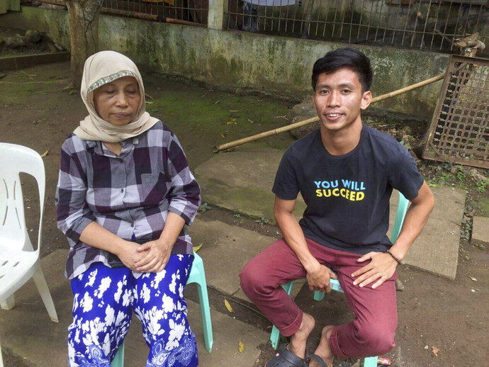 In this photo provided by the Armed Forces of the Philippines, Western Mindanao Command chief Maj. Gen. Cirilito Sobejana; Filipino suicide bomber Norman Lasuca sits with his mother Vilman. On Wednesday, July 10, 2019. Military and police officials say a DNA test has confirmed the identity of the first known Filipino suicide bomber named as Norman Lasuca. Two attackers carrying explosives killed three soldiers, two villagers and themselves and wounded 22 others in a June 28 attack on an army camp in southern Sulu province. The second attacker remains unidentified. (Armed Forces of the Philippines Via AP)