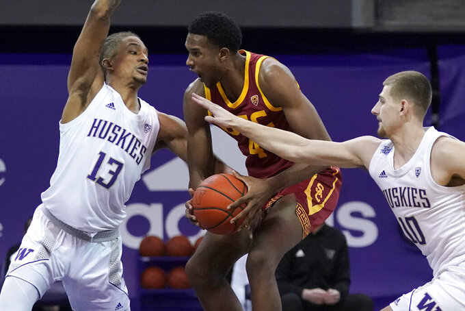 Southern California forward Evan Mobley, center, drives between Washington forward Hameir Wright (13) and guard Erik Stevenson (10) during the first half of an NCAA college basketball game Thursday, Feb. 11, 2021, in Seattle. (AP Photo/Ted S. Warren)