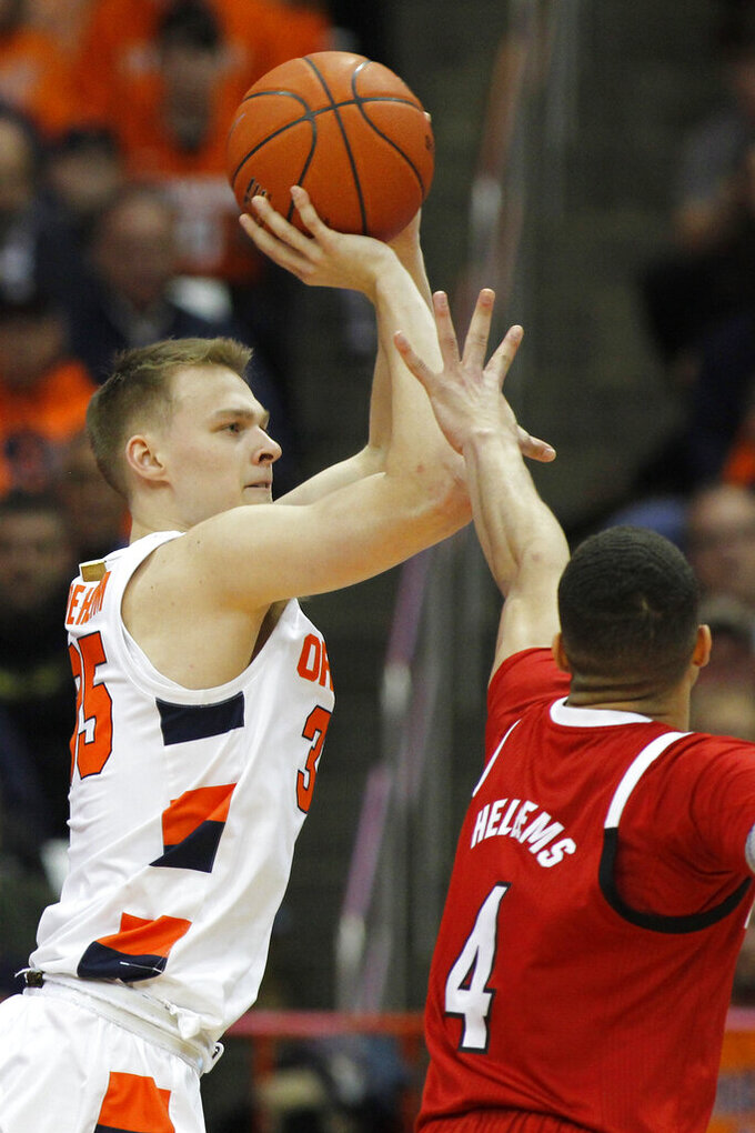 Syracuse's Buddy Boeheim, left, shoots over North Carolina State's Jericole Hellems, right, in the first half of an NCAA college basketball game in Syracuse, N.Y., Tuesday, Feb. 11, 2020. (AP Photo/Nick Lisi)