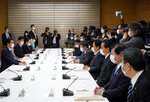 Japanese Prime Minister Shinzo Abe, left, speaks during a meeting of the headquarters for measures against the coronavirus disease at the prime minister official residence in Tokyo, Japan, Monday, April 6, 2020.  Abe said that he will declare a state of emergency for Tokyo and six other prefectures as early as Tuesday to bolster measures to fight the coronavirus outbreak, but that there will be no hard lockdowns. (Franck Robichon/Pool Photo via AP)