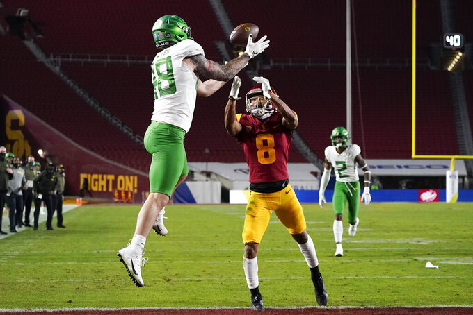 Oregon tight end Hunter Kampmoyer (48) catches a pass in the end zone for a touchdown against Southern California cornerback Chris Steele (8) during the first quarter of an NCAA college football game for the Pac-12 Conference championship Friday, Dec 18, 2020, in Los Angeles. (AP Photo/Ashley Landis)