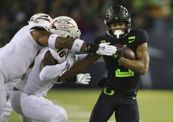 Oregon's Johnny Johnson III, right, is tackled by Arizona State's Jay Jay Wilson, left, and Aashari Crosswell during the second quarter of an NCAA college football game Saturday, Nov. 17, 2018, in Eugene, Ore. (AP Photo/Chris Pietsch)