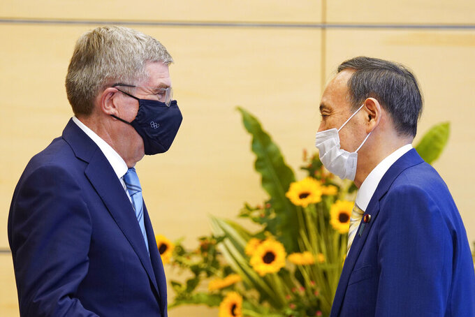 International Olympic Committee President Thomas Bach, left, meets Japanese Prime Minister Yoshihide Suga during his courtesy call at the latter's official residence in Tokyo Wednesday, July 14, 2021. (Kimimasa Mayama/Pool Photo via AP)