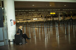 A passenger, wearing a mouth mask to protect against the spread of coronavirus, waits at a nearly empty check-in area at the Brussels International Airport in Brussels, Tuesday, May 12, 2020. (AP Photo/Francisco Seco)