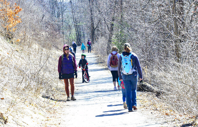 People get some exercise on a sunny day at the West River Trail, in Brattleboro Vt., as they try to keep some distance during the COVID-19 outbreak on Saturday, March 21, 2020. (Kristopher Radder/The Brattleboro Reformer via AP)