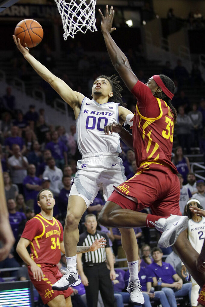 FILE - Kansas State guard Mike McGuirl (00) makes a basket while covered by Iowa State forward Solomon Young (33) during the second half of an NCAA college basketball game in Manhattan, Kan., in tis Saturday, March 7, 2020, file photo. (AP Photo/Orlin Wagner)