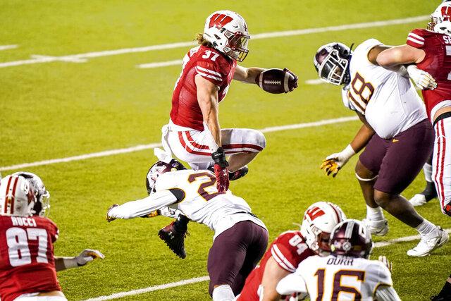 Wisconsin running back Garrett Groshek (37) runs over Minnesota defensive back Tyler Nubin (27) during overtime of an NCAA college football game Saturday, Dec. 19, 2020, in Madison, Wis. (AP Photo/Andy Manis)