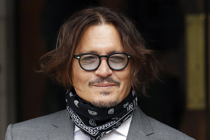 """American actor Johnny Depp poses for the media as he arrives at the High Court in London, Monday, July 13, 2020.  Depp is expected to wrap up his evidence at his libel trial against a tabloid newspaper that accused him of abusing ex-wife Amber Heard. The Hollywood star is suing News Group Newspapers, publisher of The Sun, and the paper's executive editor, Dan Wootton, over an April 2018 article that called him a """"wife-beater.""""  (AP Photo/Matt Dunham)"""