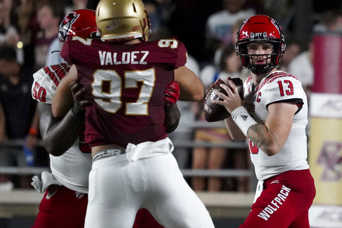 North Carolina State quarterback Devin Leary (13) drops back to pass as teammate Grant Gibson(50) blocks Boston College defensive end Marcus Valdez (97) during the first half of an NCAA college football game, Saturday, Oct. 16, 2021, in Boston. (AP Photo/Mary Schwalm)