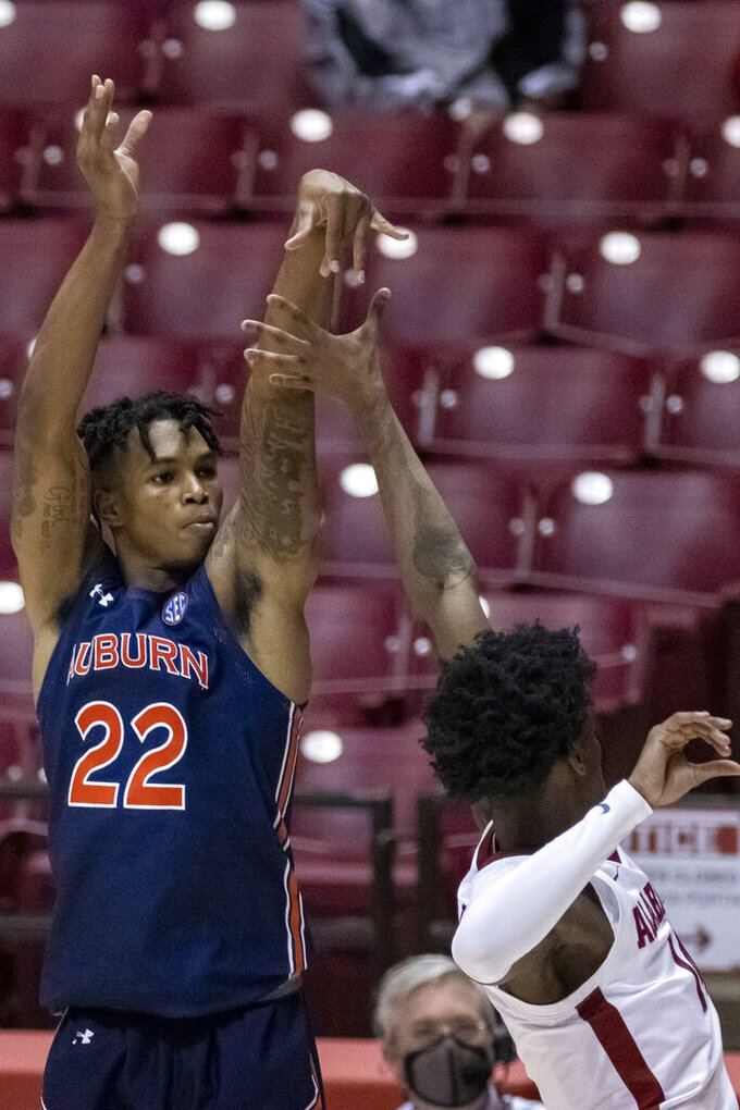 Auburn guard Allen Flanigan (22) shoots over Alabama guard Keon Ellis (14) during the first half of an NCAA college basketball game Tuesday, March 2, 2021, in Tuscaloosa, Ala. (AP Photo/Vasha Hunt)